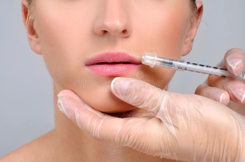 Woman is getting botox injection n lips. Cosmetic Treatment and Plastic Surgery. Woman is getting botox injection in lips. Cosmetic Treatment. Plastic Surgery royalty free stock images