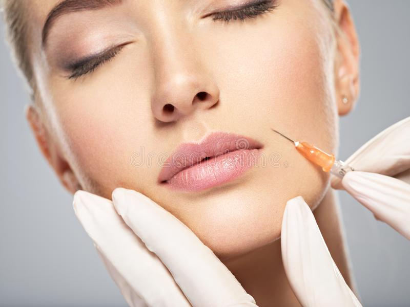 Woman getting cosmetic injection of botox in cheek. Closeup. Woman in beauty salon. plastic surgery clinic royalty free stock images