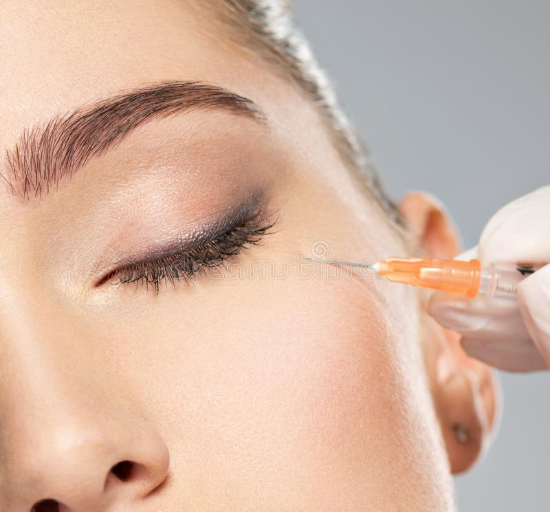 Woman getting cosmetic injection of botox near eyes stock image