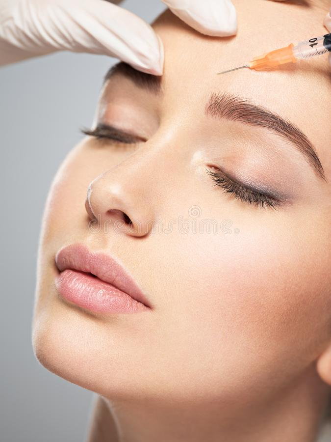 Woman getting cosmetic injection of botox near eyes stock images