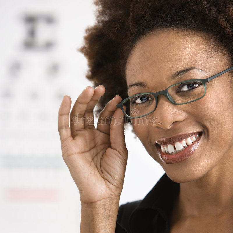 Woman getting eyeglasses. Portrait of woman with afro wearing eyeglasses with medical eyechart in background royalty free stock image