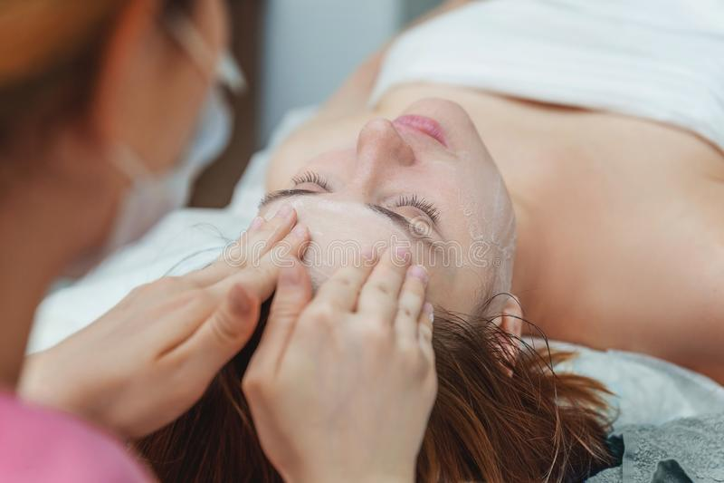 Woman getting face treatment with white nourishing creme in spa salon royalty free stock image