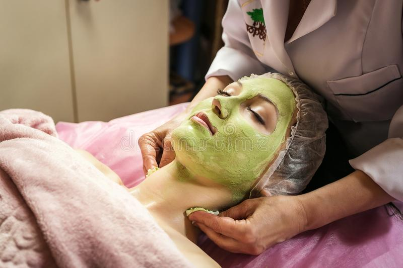woman getting facial care peeling mask by beautician at spa salon royalty free stock image