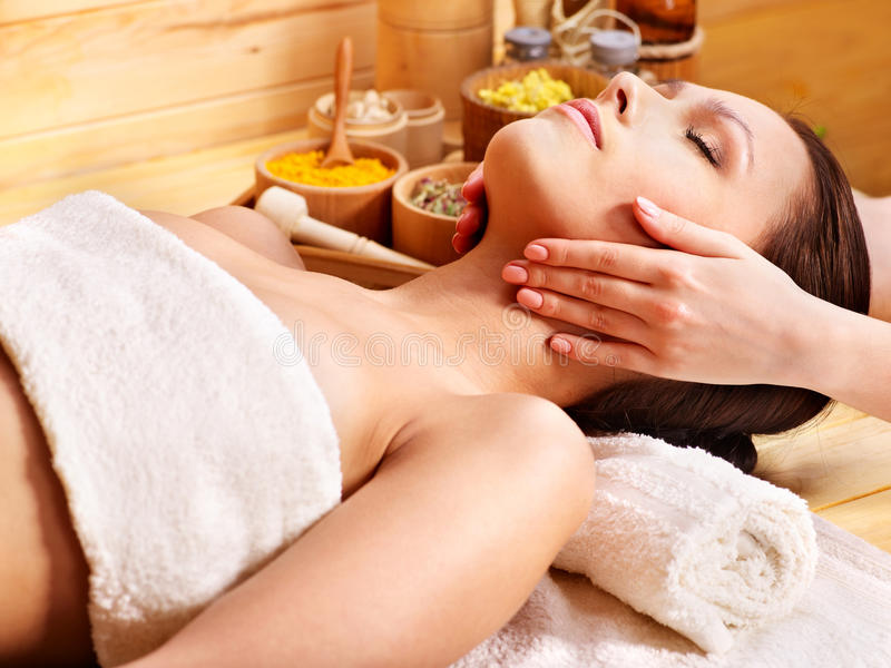 Woman getting facial massage . Woman getting facial massage in wooden spa stock photos