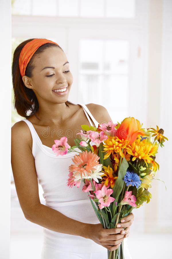 Woman getting flower. Happy ethnic woman getting bouquet of colorful flowers royalty free stock image