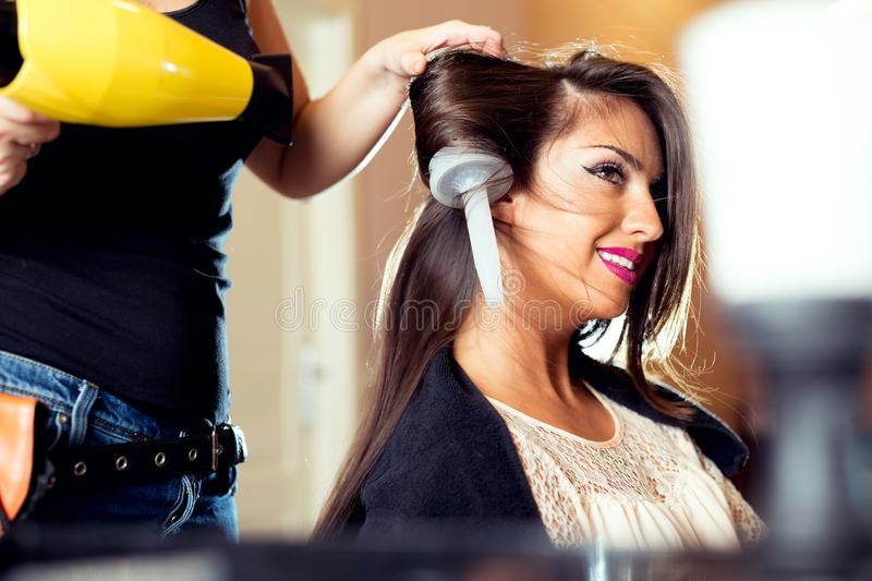 Woman getting her hair dried at the hair salon stock images