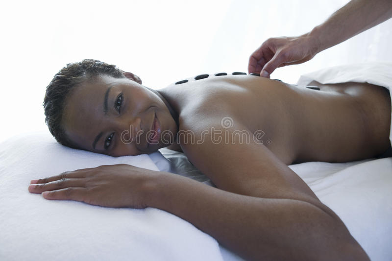 Woman Getting A Hot Stone Massage At Spa stock image