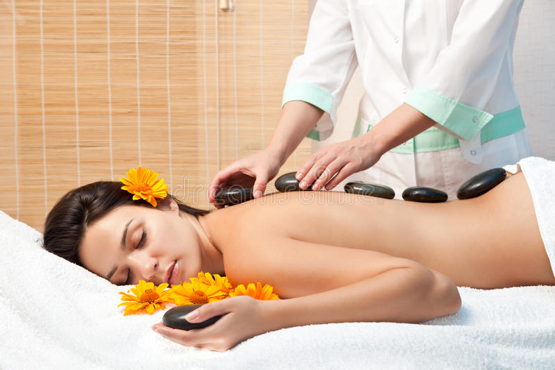 Woman getting a hot stone massage at spa salon stock photos