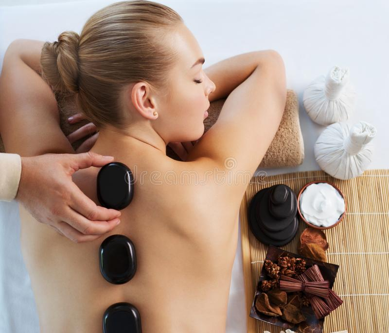Woman getting hot stone massage in spa salon. royalty free stock images