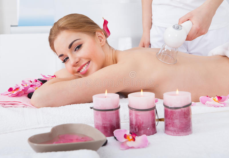 Woman getting laser therapy. Smiling Young Woman Getting Laser Therapy In Spa stock image