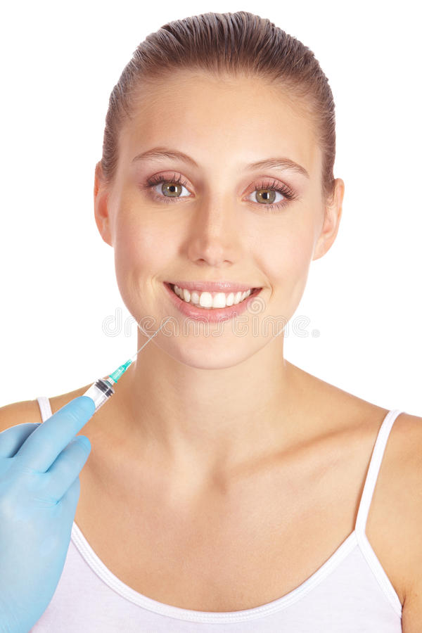 Woman getting lip augmentation. Smiling woman getting lip augmentation with syringe stock photos