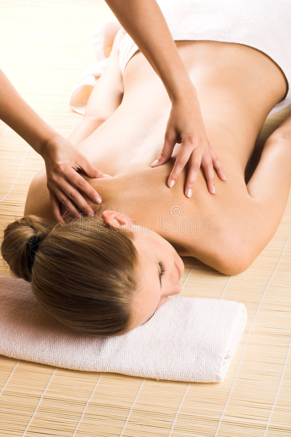 Woman getting a massage. Young beautiful woman in a spa is getting a massage stock images