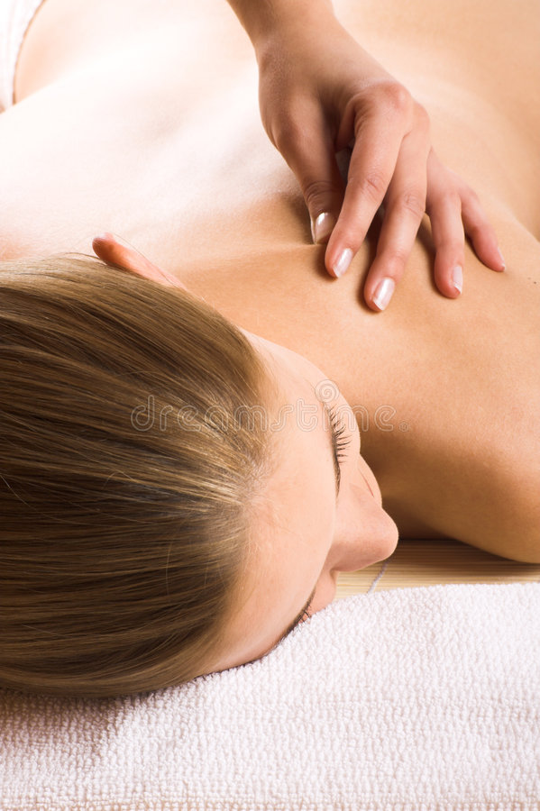 Woman getting a massage. Young beautiful woman in a spa is getting a massage stock photography
