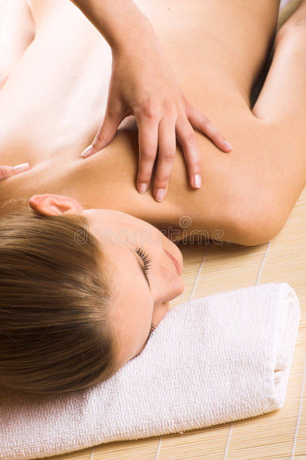 Woman getting a massage. Young beautiful woman in a spa is getting a massage stock photo