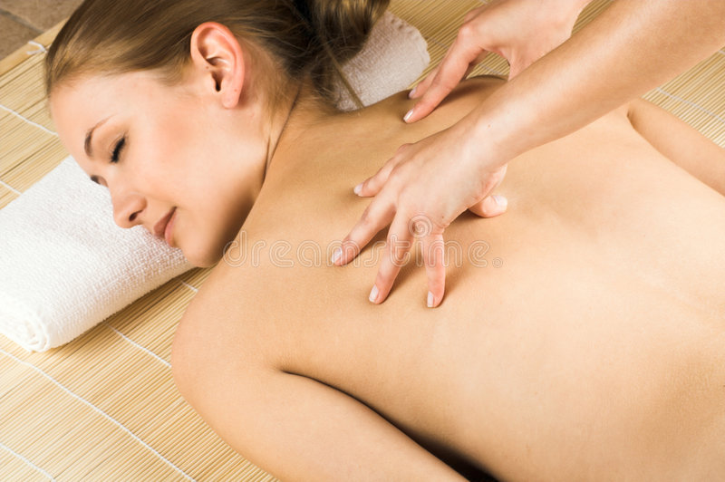 Woman getting a massage. Young beautiful woman in a spa is getting a massage stock image