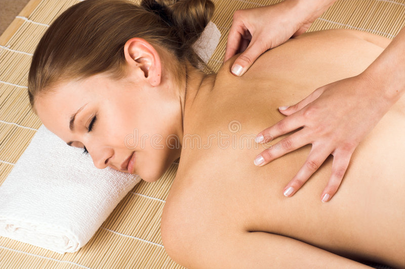 Woman getting a massage. Young beautiful woman in a spa is getting a massage royalty free stock photo