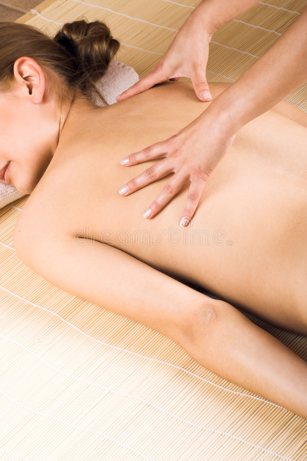 Woman getting a massage. Young beautiful woman in a spa is getting a massage royalty free stock photography