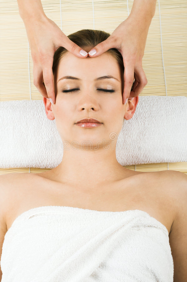 Woman getting a massage. Young beautiful woman in a spa is getting a massage royalty free stock images