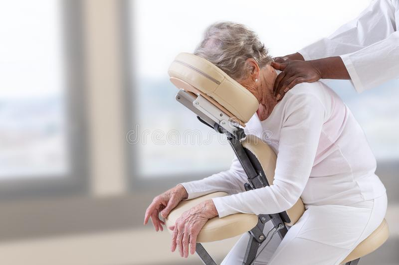 Senior woman getting massage in chair in therapy room stock photo