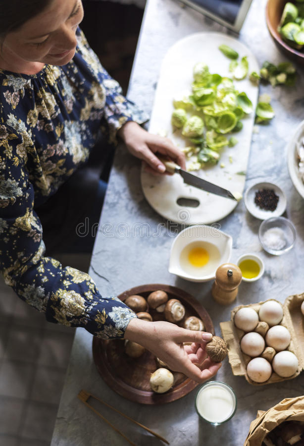 Woman getting mushroom to cook royalty free stock image
