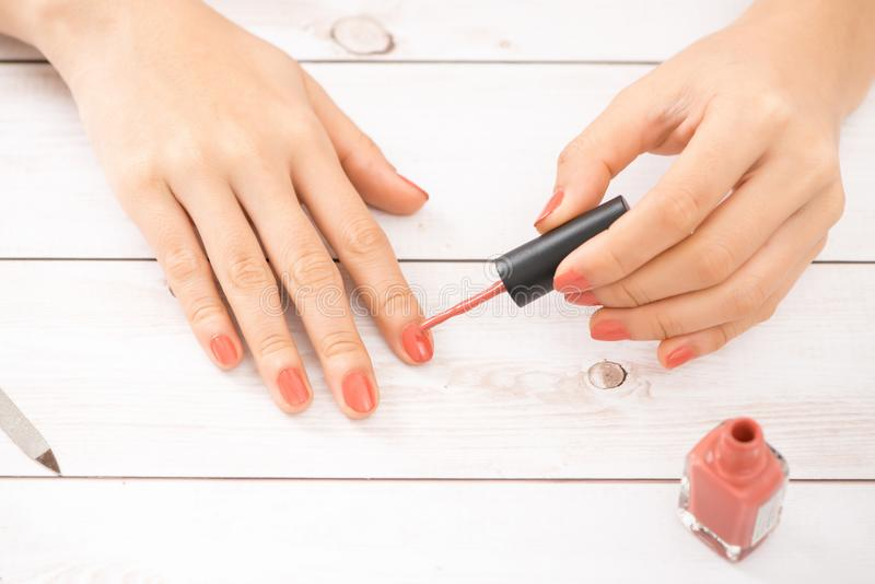 Woman getting nail manicure. Manicurist applying red nail polish. royalty free stock images
