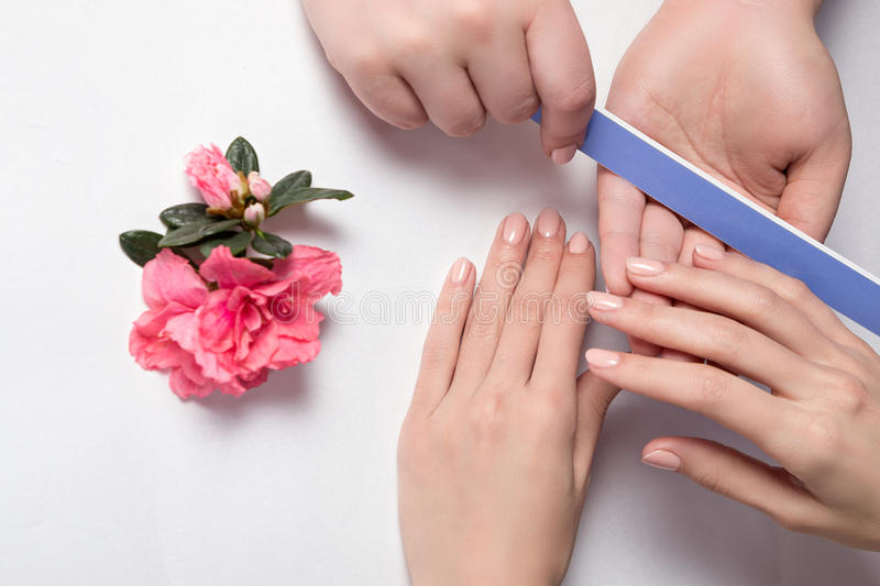 Woman getting nail manicure in salon. Closeup shot of a woman in a nail salon receiving a manicure by a beautician with nail file. Woman getting nail manicure royalty free stock photos