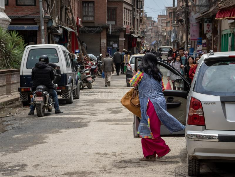 Woman Getting out of Car. Kathmandu, Nepal - April 7, 2019: A woman getting out of a car in the UNESCO World Heritage Site of Patan Durbar Marg in Kathmandu royalty free stock images