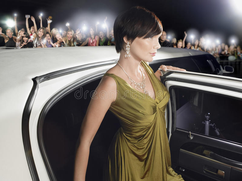 Woman Getting Out Of Limousine In Front Of Fans And Paparazzi. Beautiful young women in evening wear getting out of limousine in front of fans and paparazzi stock image