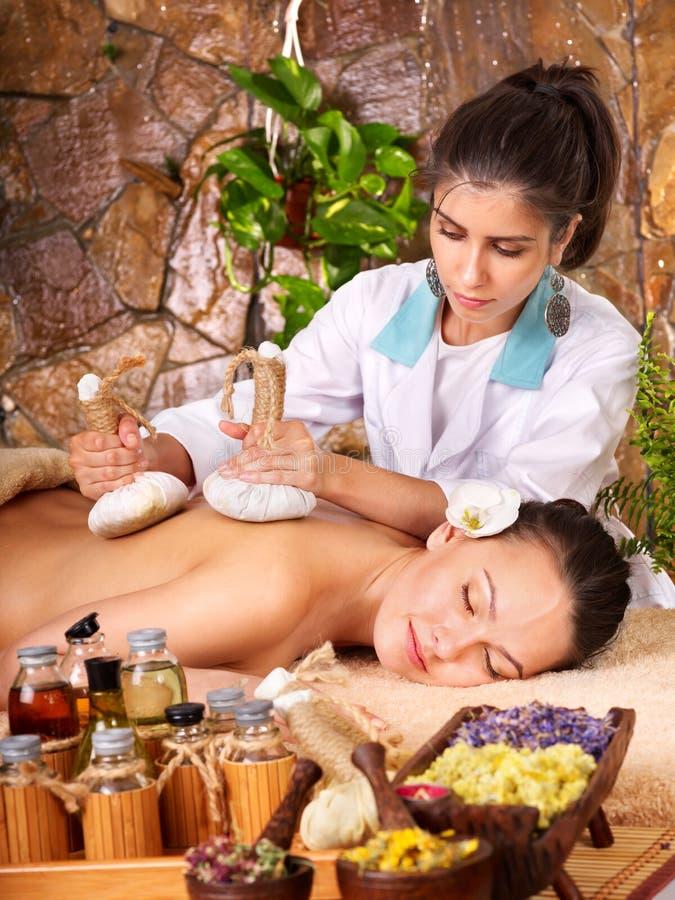 Woman getting thai herbal compress massage . Woman getting thai herbal compress massage in spa stock photo