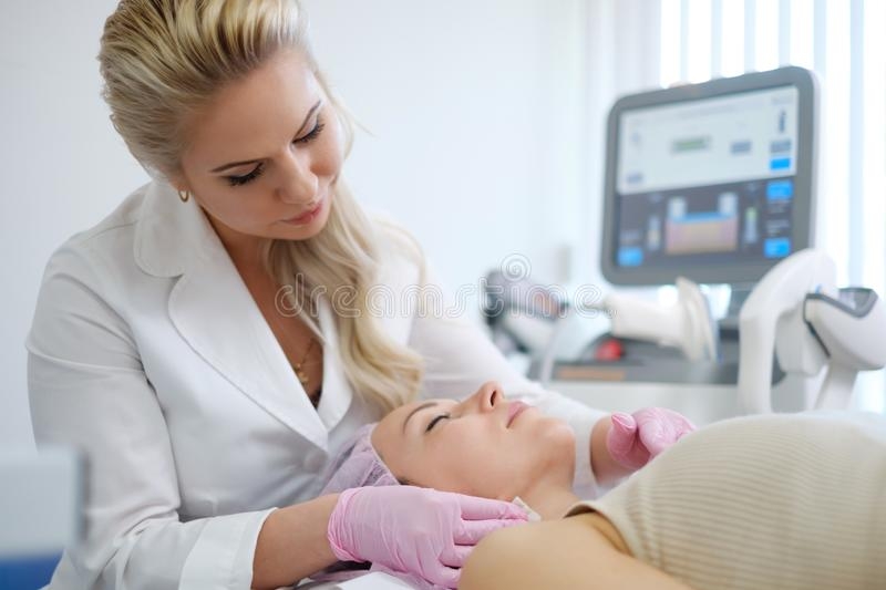 Woman getting treatment with aesthetic dermatology device.  royalty free stock image