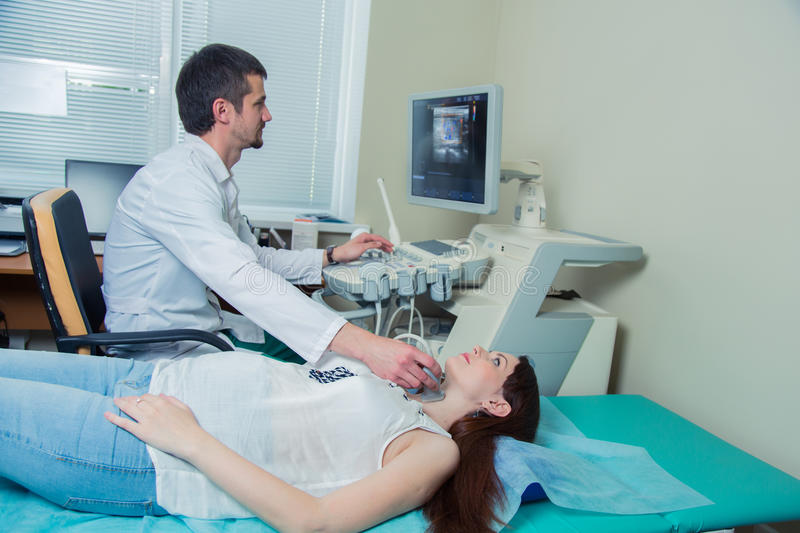 Woman getting ultrasound of a thyroid from doctor.  royalty free stock photo