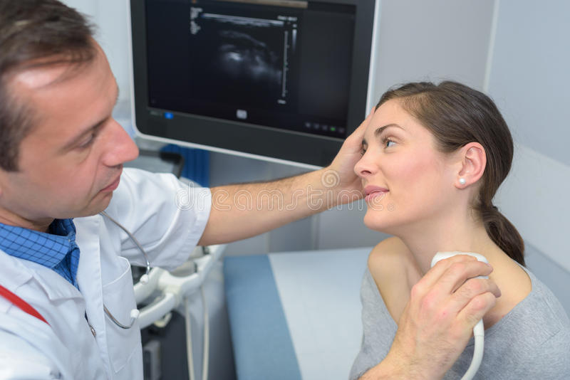 Woman getting ultrasound thyroid from doctor. Woman getting ultrasound of a thyroid from doctor stock photo