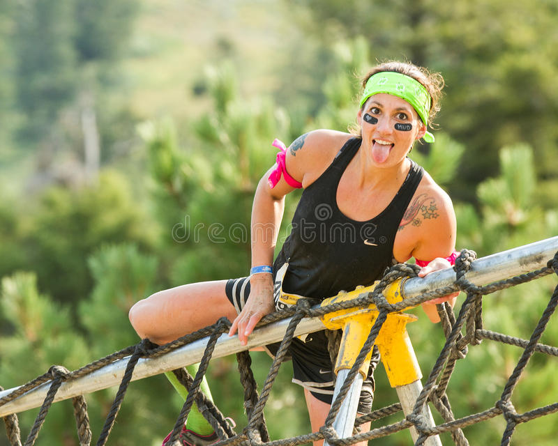 Woman getting up and over a cargo net stock photo