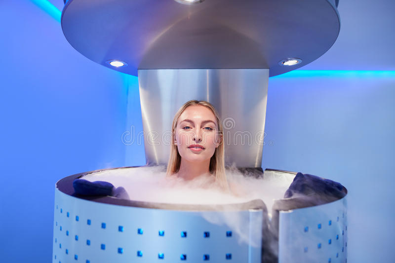 Woman getting whole body cryotherapy. Woman in cryosauna booth for whole body cryotherapy. Caucasian female in freezing chamber with nitrogen vapors stock image