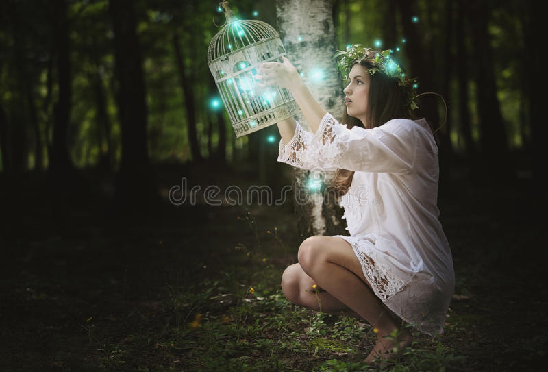 Woman with ghost lights in secret forest stock photo