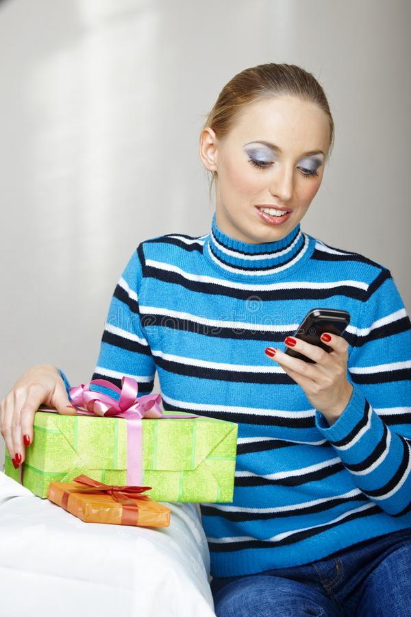 Woman with gift box using smartphone stock photo