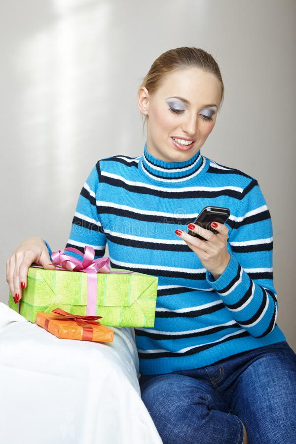 Woman with gift box using smartphone stock photography