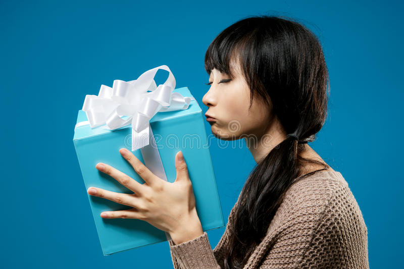 Woman with gift. Young woman holding gift box and kiss it, closeup portrait on studio blue background royalty free stock images