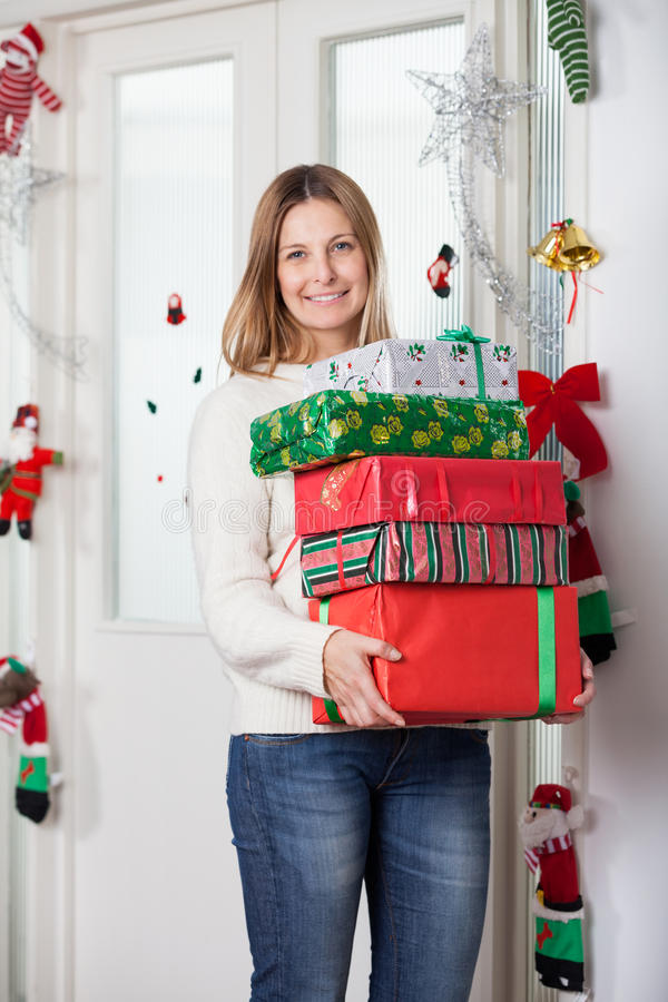 Woman With Gifts Standing By Door During Christmas royalty free stock photo