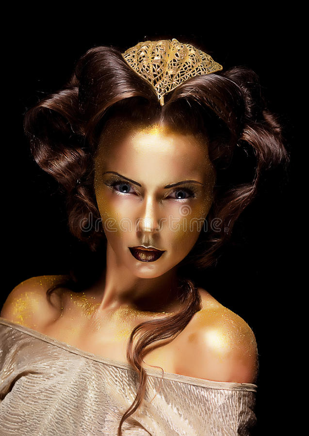 Woman gilded golden face - theater luxury make up. Dramatic style. Woman gilded gold face - theater luxury make up royalty free stock photography