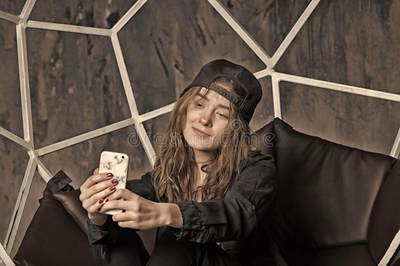 Woman in baseball cap making selfie with smartphone royalty free stock image