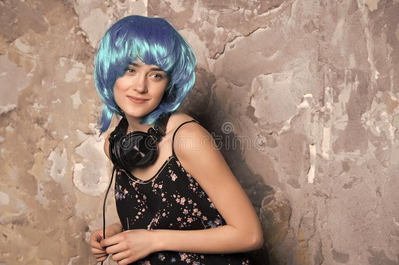 Woman in blue wig smiling with headphones on cement wall stock image