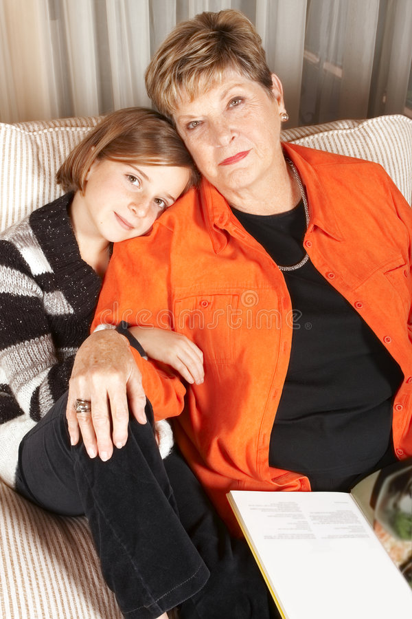 Woman and girl with book on sofa stock images