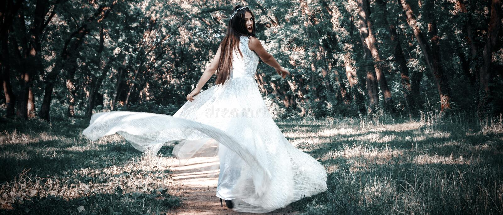 Woman or girl, a bride in a white wedding dress, stands in the m. Iddle of a forest or park, a mysterious photo, dress flying stock images
