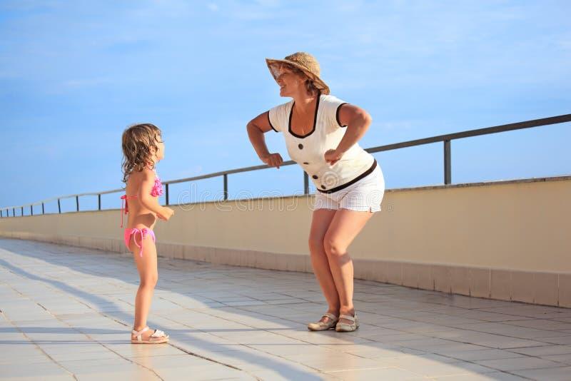 Woman and girl do morning exercise on veranda stock photos