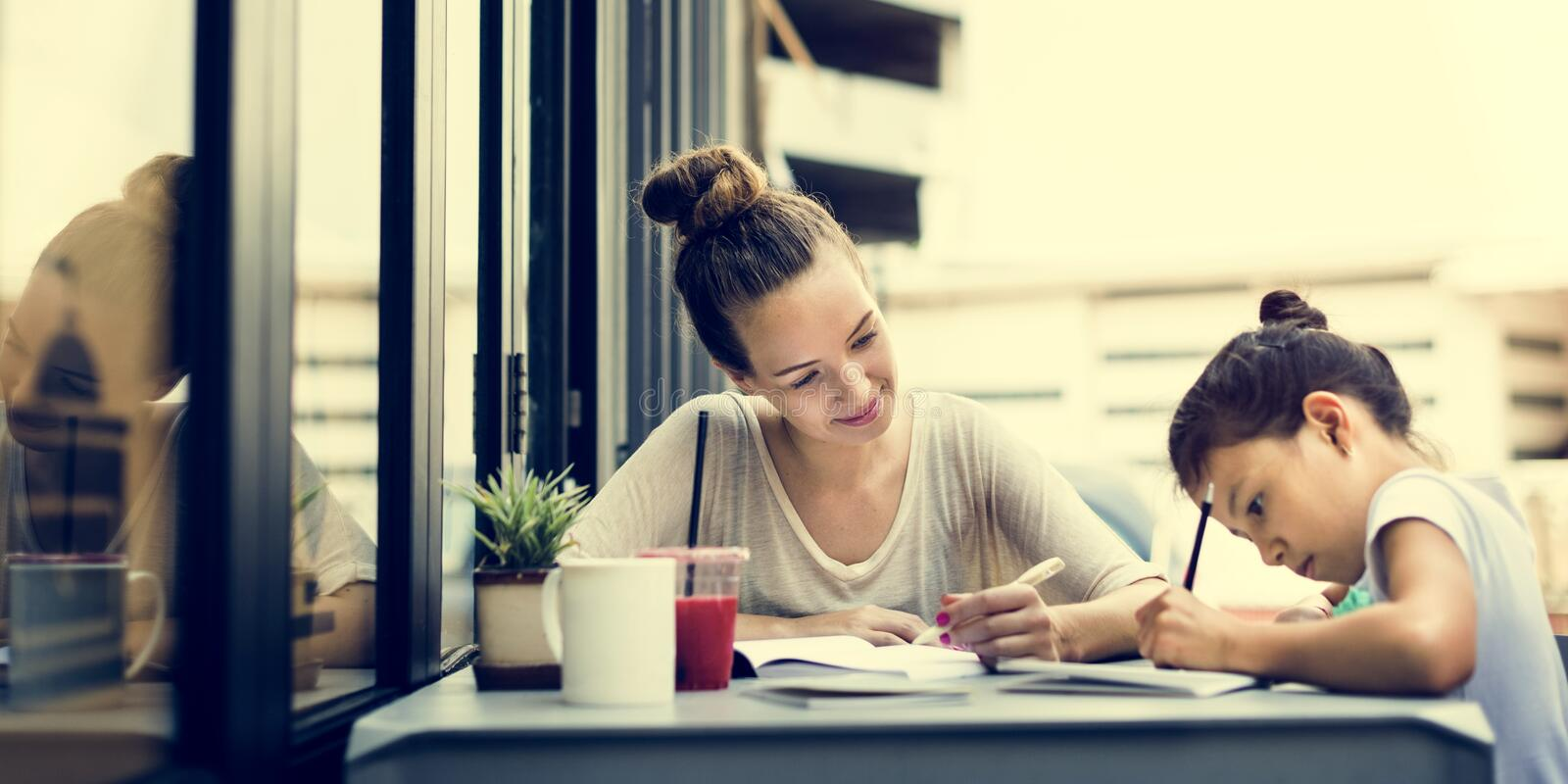 Woman And Girl Doing Homework Concept stock images