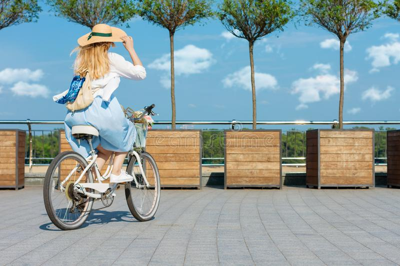 Woman is cycling in blue dress on white bicycle with basket of flowers stock photo