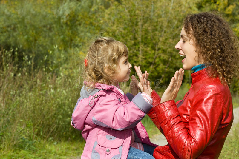 Woman and girl playing in okie dokey in garden stock photo