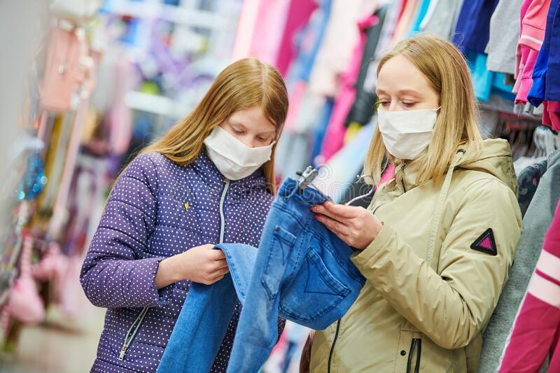 Woman and girl in protective mask shopping clothing jeans pants in apparel shop at coronavirus epidemic stock photos