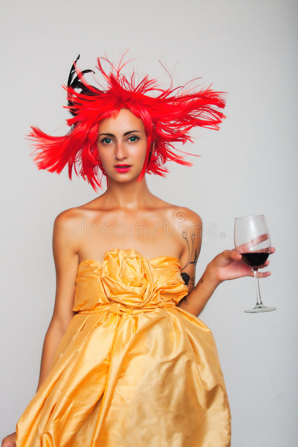 Woman girl in red wig posing with glass of wine royalty free stock images